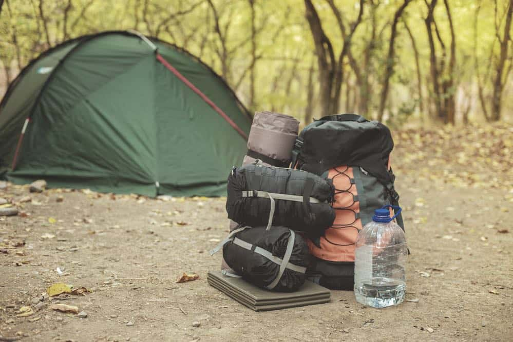 backpack sleeping bags next to a hiking bag with a tent in the background in the woods