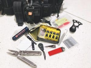 survival kit items displayed on the floor next to an altoids tin