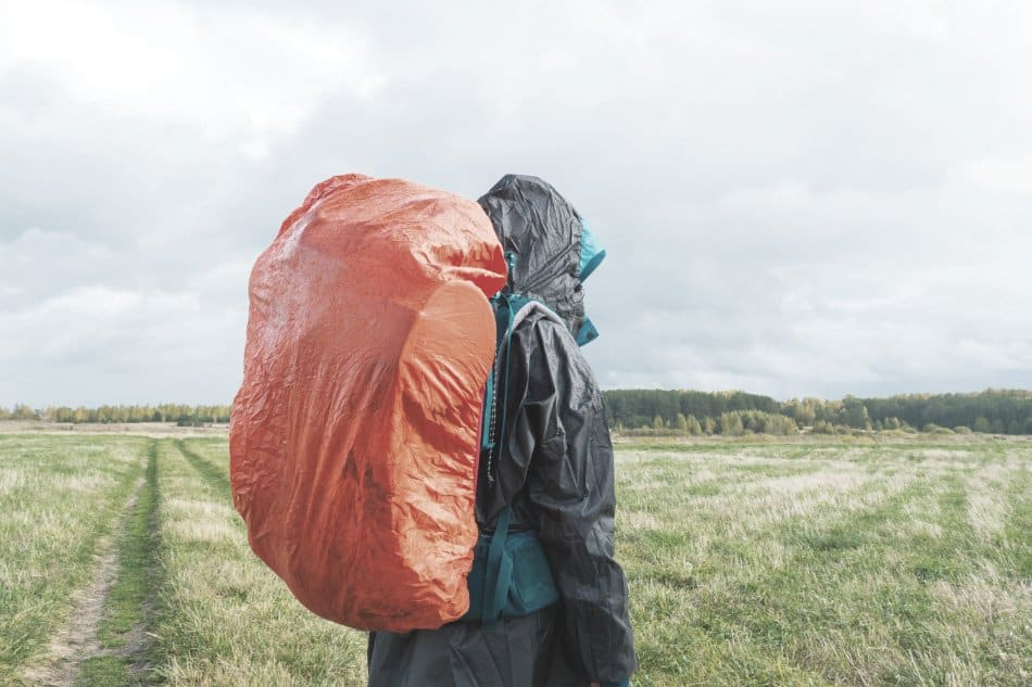 man wearing backpack in rain with rain cover