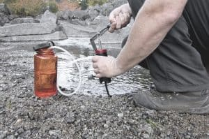 man filling water bottle with filtered water from the river