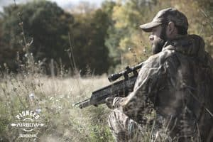 hunter standing in brush holding airbow ready to hunt