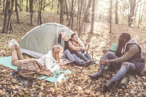 4 adult friends sitting by their tent in the woods laughing