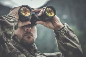 hunting man looking through binoculars