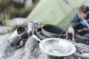 camping cookware in focus as man sitting in background is preparing his winter camping tent