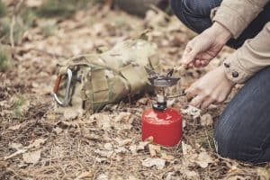 person in wilderness ignites camping stove to boil water