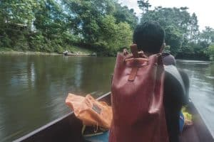 man sitting gin a boat with a dry bag backpack on his back on a river boat