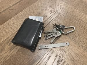 wallet and set of keys set on floor next to edc pry bar for everyday carry