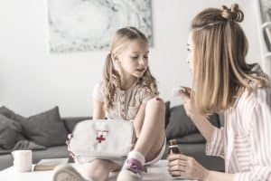 mother treating little girls cut on her knee while holding home first aid kit