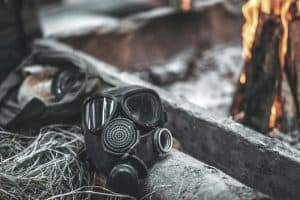 gas mask with respirator used in an emergency situation set on floor near fire