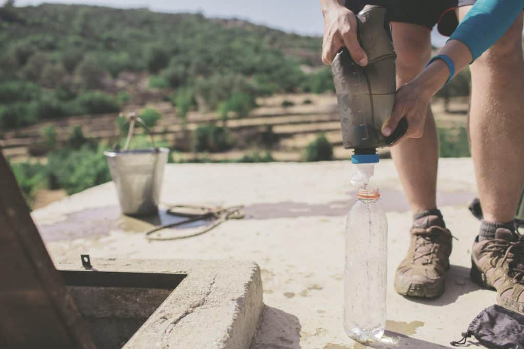 man filling water bottle from a gravity water filter while hiking outdoors