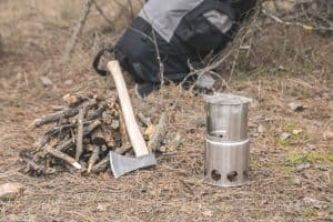 camping hatchet axe leaning on timber next to camp fire in woods