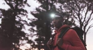 man standing in woods with backpack and headlamp on head
