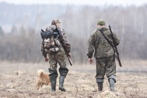 hunters walking through the woods carrying their hunting backpacks
