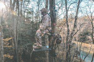 a man standing patiently in a hunting treestand waiting for his prey