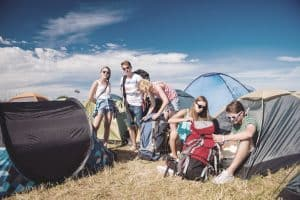 friends gathered by their pop up tents at an outdoor festival
