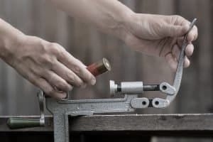man reloading a shotgun shell with a progressive press