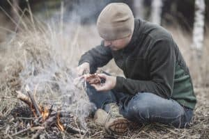 man in the wilderness cooking a bird on an open fire