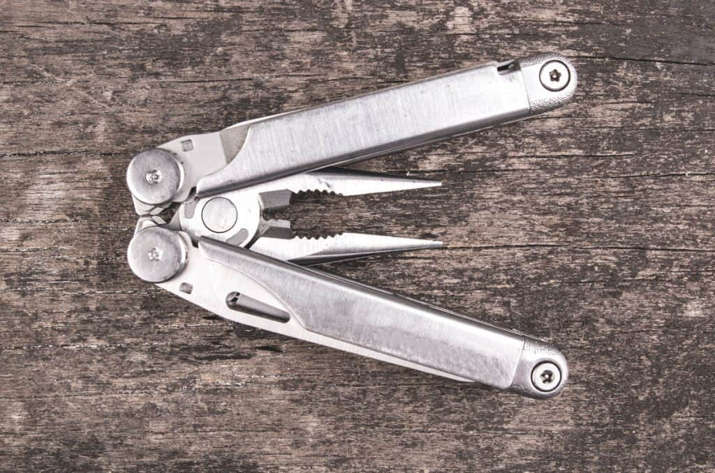 survival multi tool set down on a wooden surface open displaying pliers
