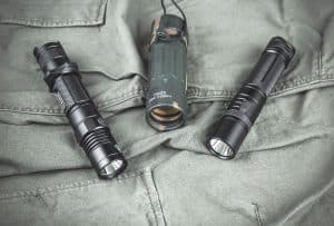tactical flashlights set down on military garment