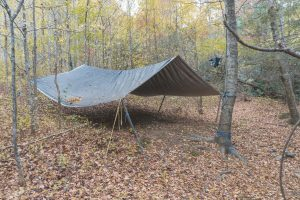 bushcraft survival shelter in the woods using a tarp