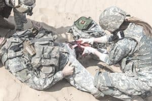 soldier is being rescued by medics using a tourniquet to stop the bleeding