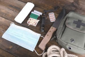 wilderness survival kit contents and bag laid out on table