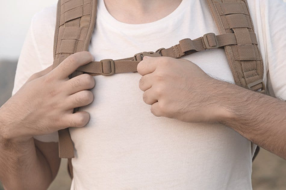 man adjusting sternum strap on backpack