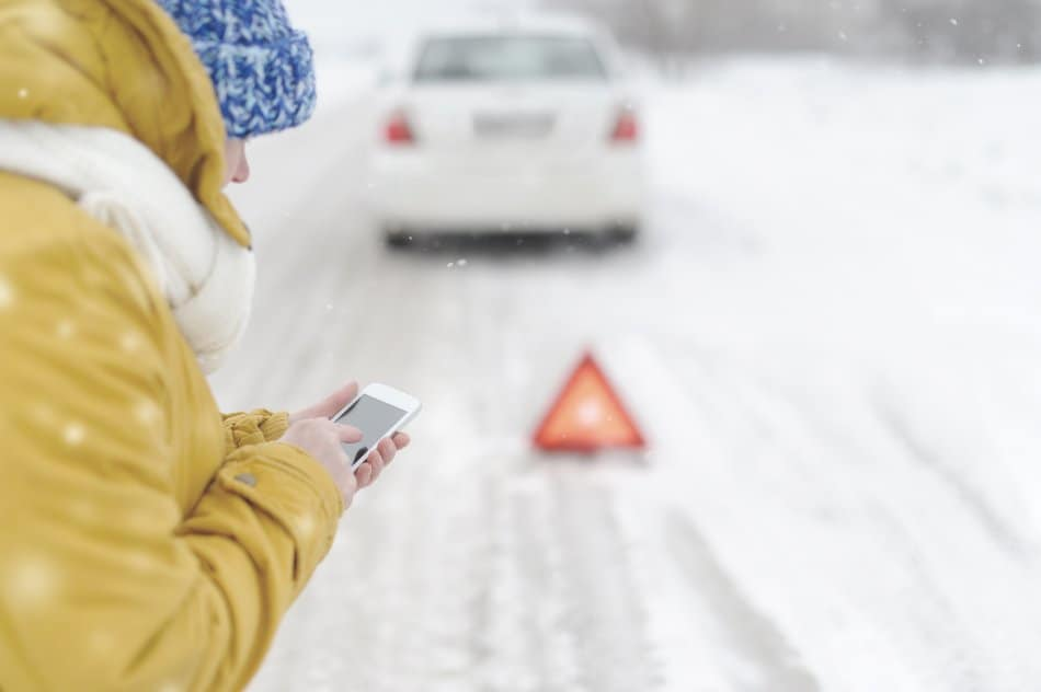 young woman calling emergency services after car break down in the snow