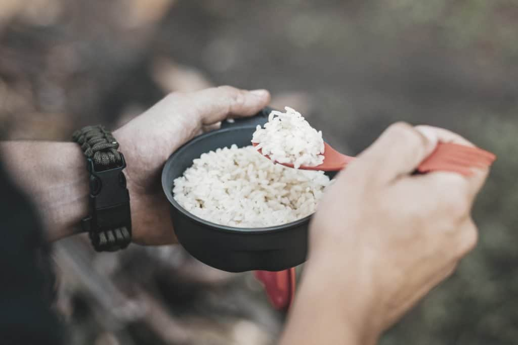 man is eating rice with camping utensils while sitting in the forest