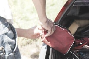 a man is placing a first aid kit in the trunk of his car