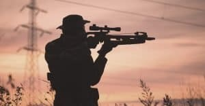silhouette of a man holding a crossbow during a sun set