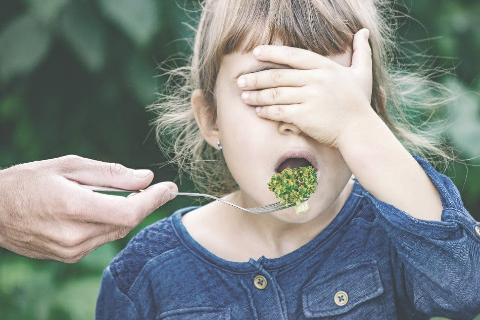 child eating vegetable with eyes closed