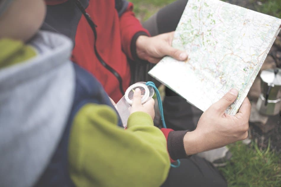 dad holding map and boy holding compass in woods