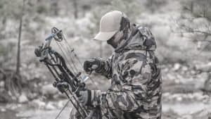 Man in camo loading a compound bow