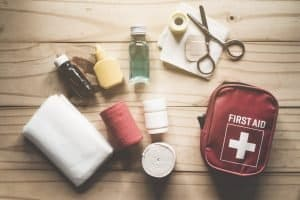 first aid kit bag and emergency contents laid on table