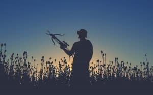 man standing in field holding a crossbow