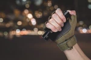 man wearing tactical glove holding the fenix pd36r tactical flashlight at night