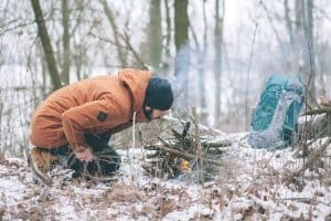 survivalist starting fire outdoors in winter