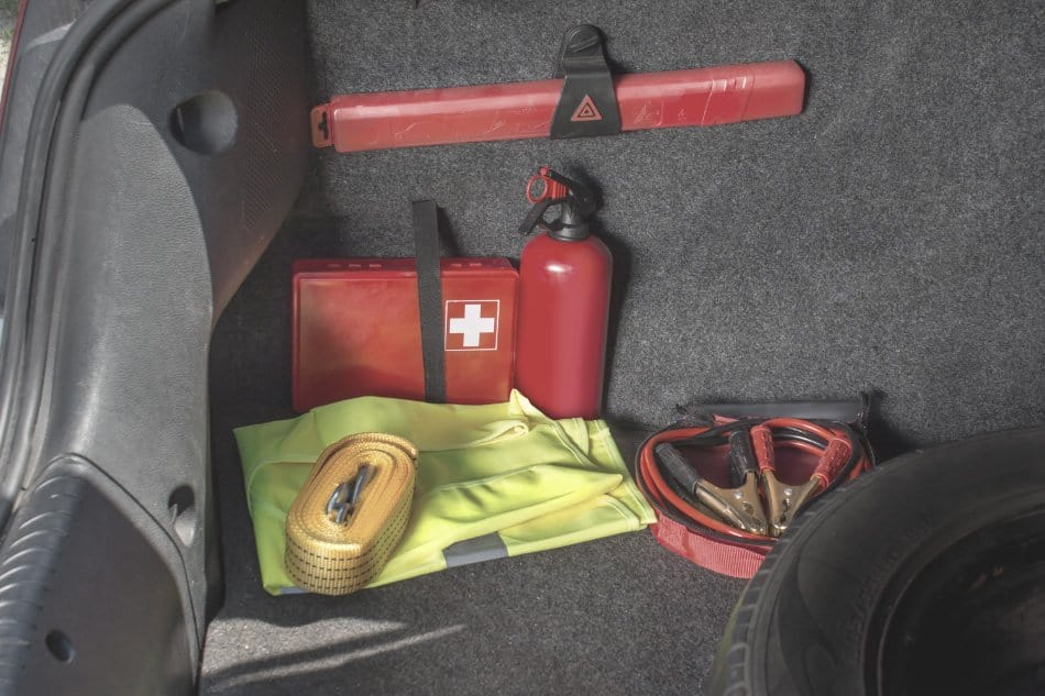 first aid kit located in trunk of car with fire extinguisher and jump leads