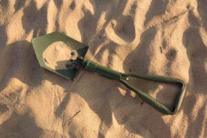 green folding shovel laying on ground in desert sand