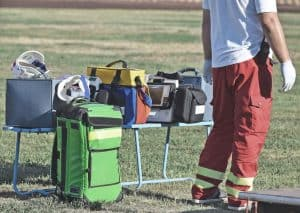 medical emergency equipment on bench with first aid backpack sitting on floor beside paramedic