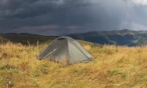 a storm is approaching while camping in the mountains with a waterproof tent