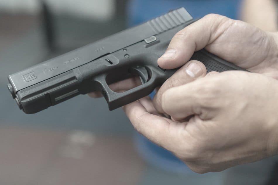 man holding glock 17 firearm in hands