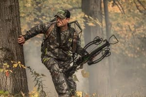 a man in the woods hunting holding a crossbow