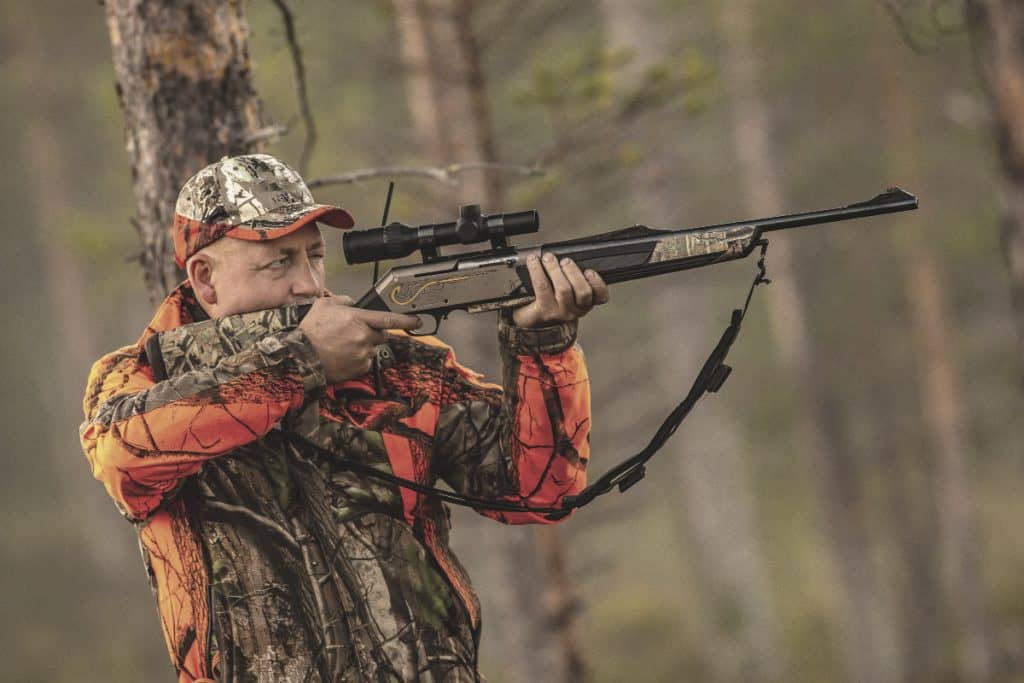 hunter in wilderness holding a rifle looking for prey