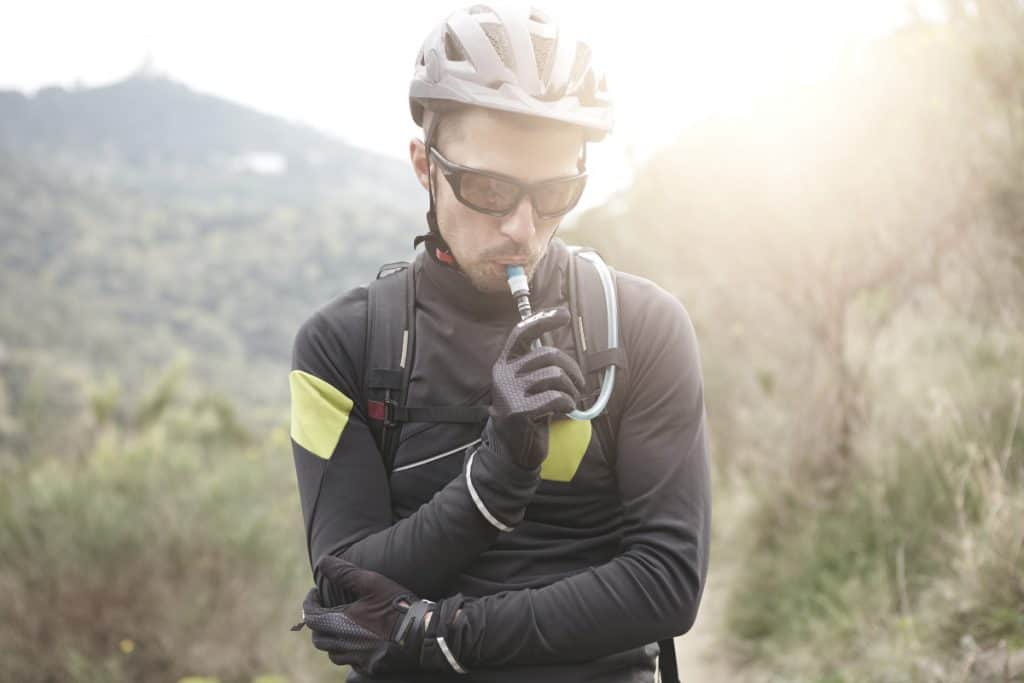 male cyclist wearing protective gear drinking from a hydration bladder while resting