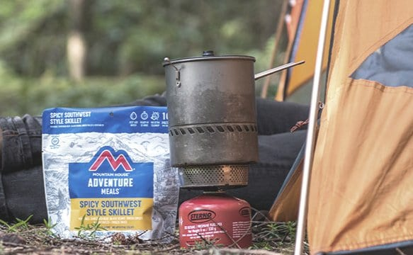 mountain house freeze dried meal pouch next to camping stove