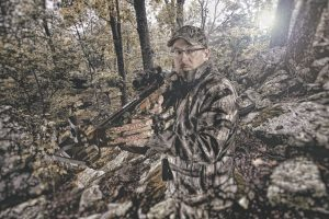 man standing in the woods holding a crossbow