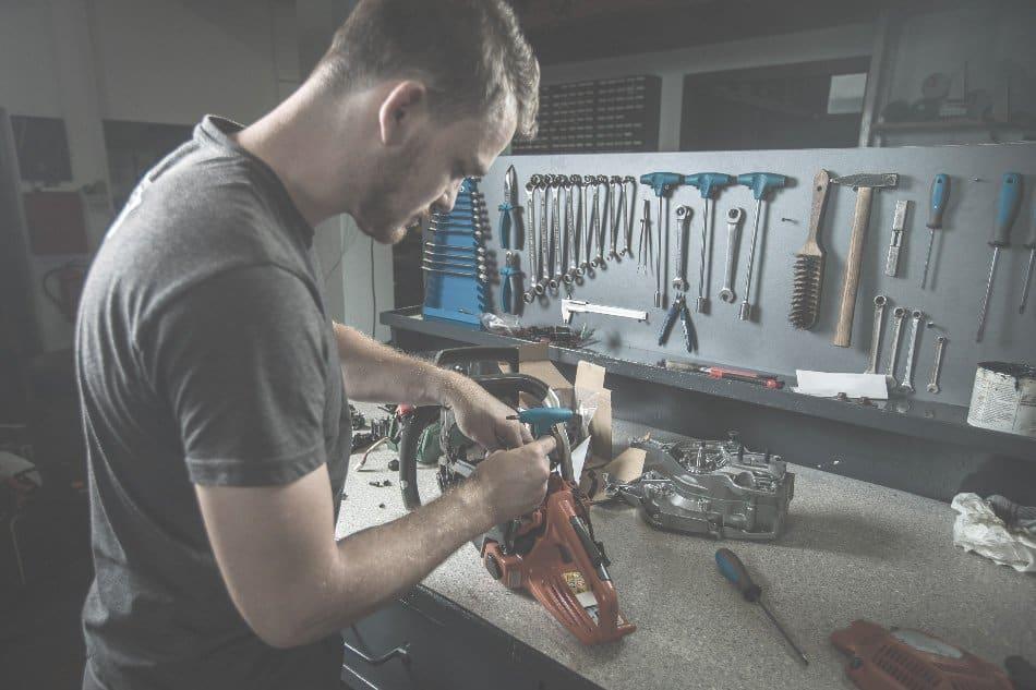 man repairing tools in workshop at home