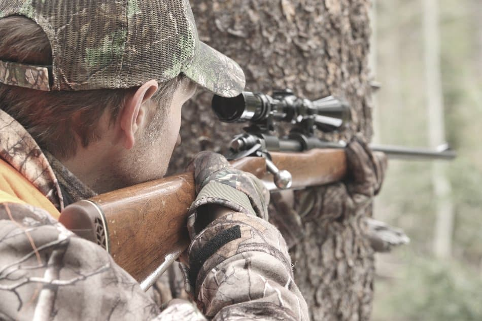 man taking aim with a hunting rifle